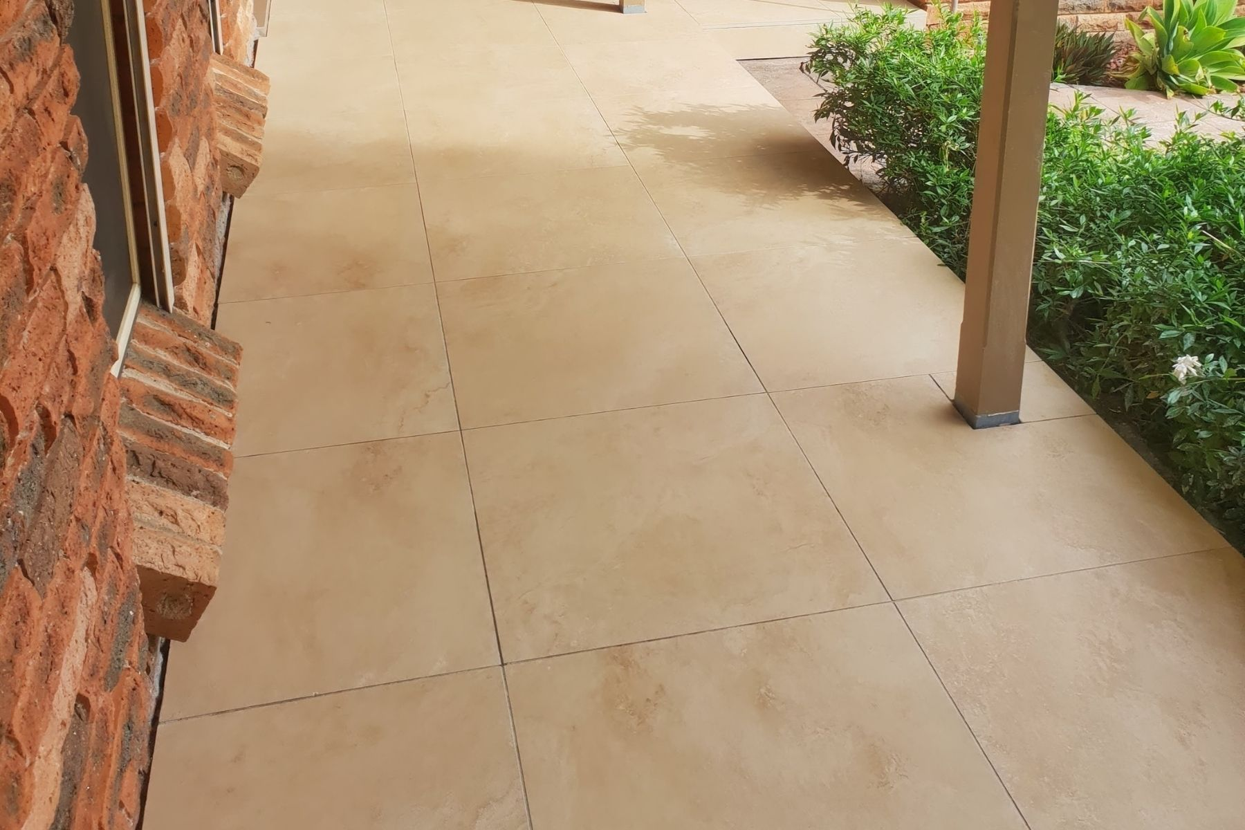 patio paved with walnut looking travertine pavers but in porcelain